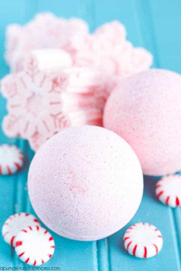 pale pink bath bombs surrounded by peppermint sweets and large pink bath bomb snowflakes