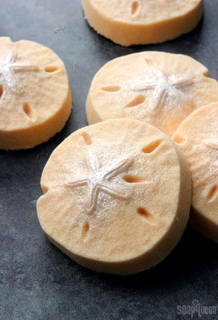 Circular bath bombs in a pale orange colour with a sea star shape on top