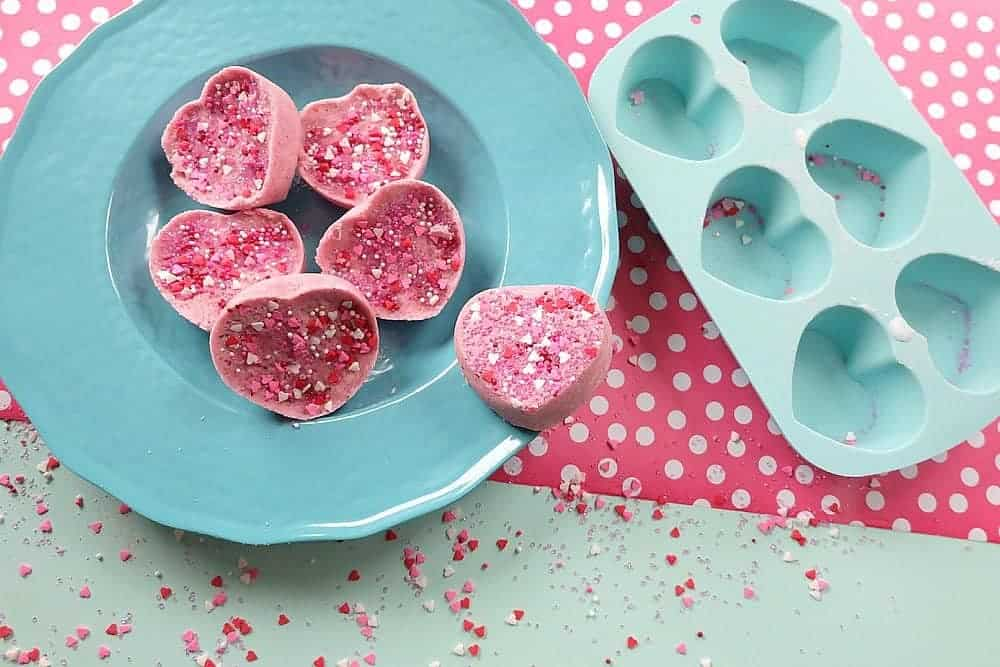 Heart bath bombs with pink sprinkles placed in a blue bowl