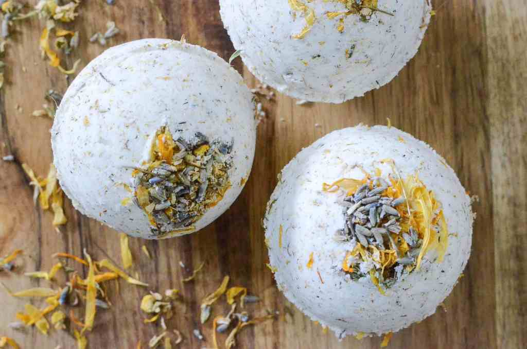 white bath bombs speckled with herbs on a table