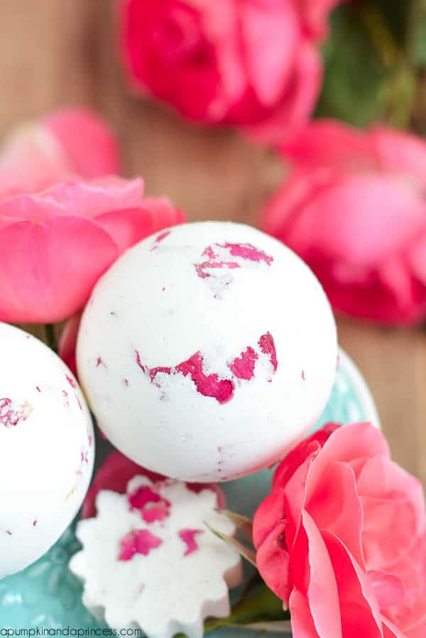 white and pink bath bombs surrounded by pink roses