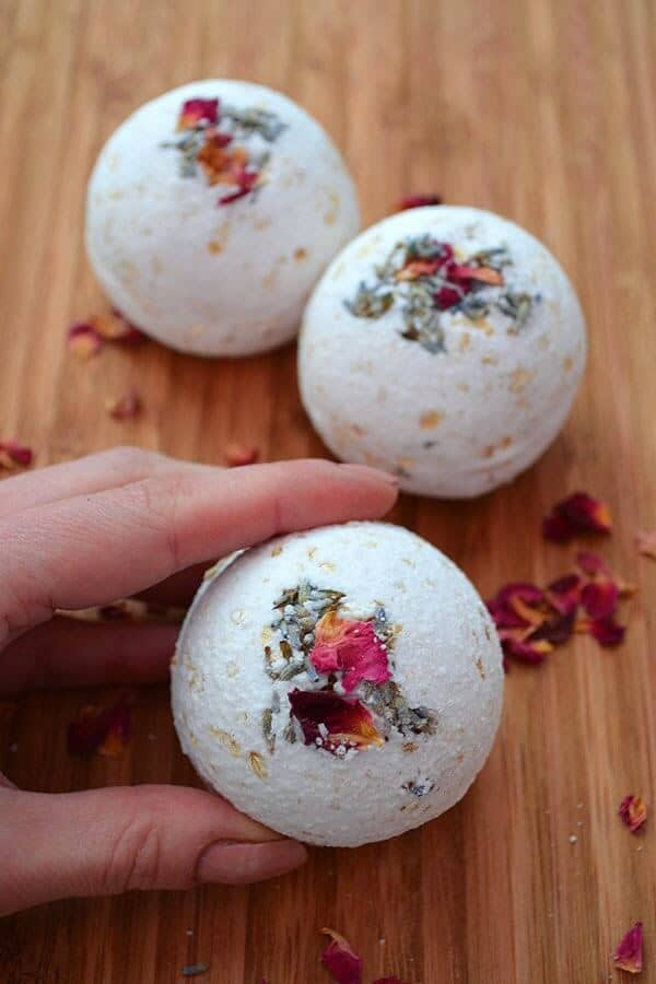 3 white bath bombs decorated with flower petals on a table