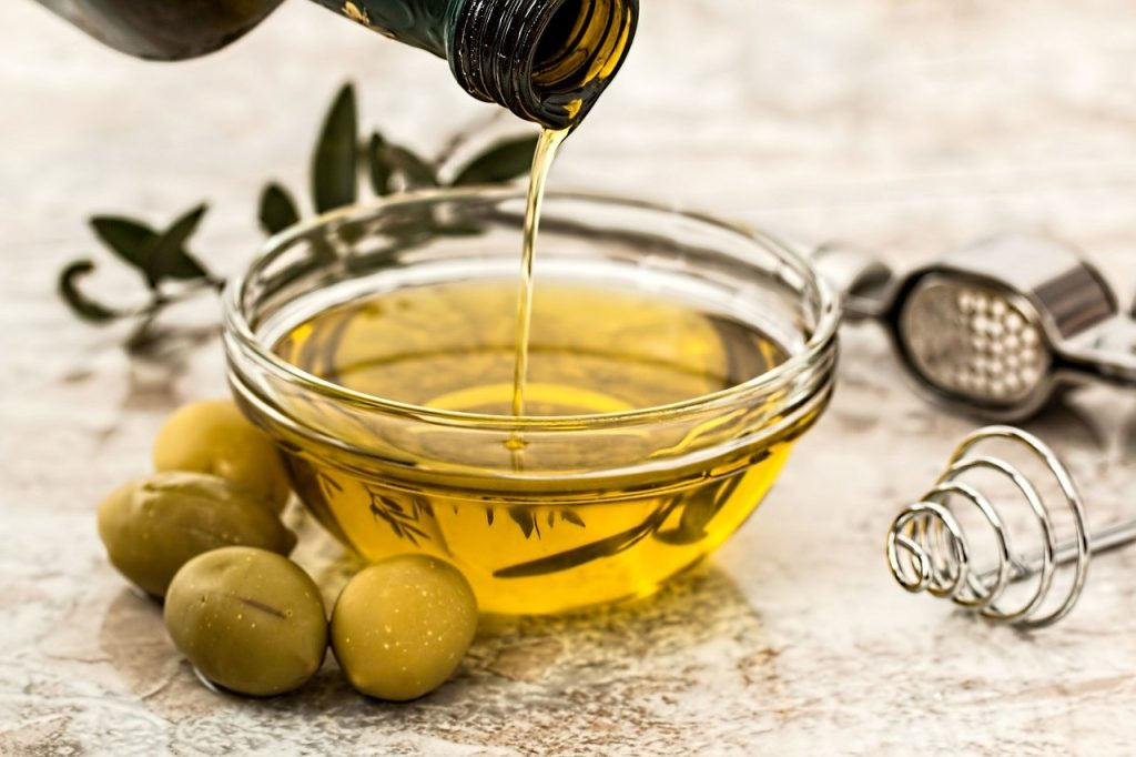 Olive oil being poured into small bowl
