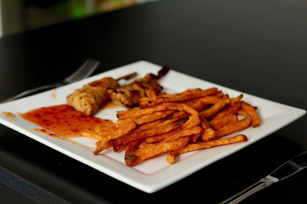 Sweet potato fries on a square plate with skewers and dipping sauce