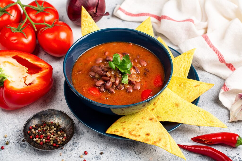 Tomato and kidney bean soup served with nachos and spices