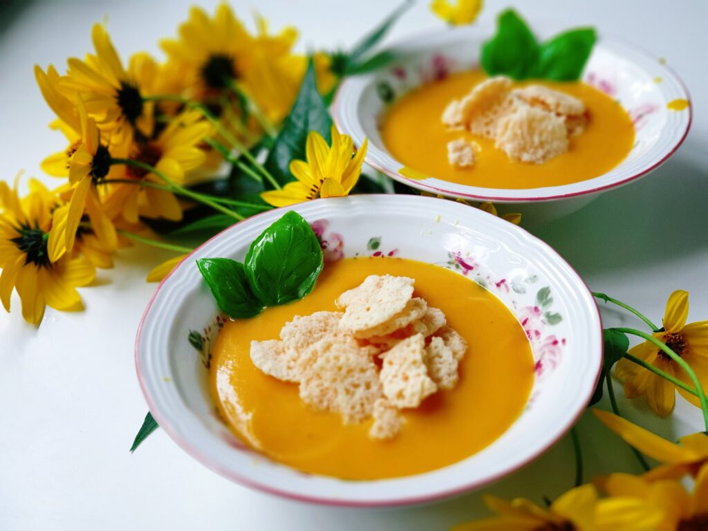 Pumpkin soup topped with croutons and basil with yellow flowers in background