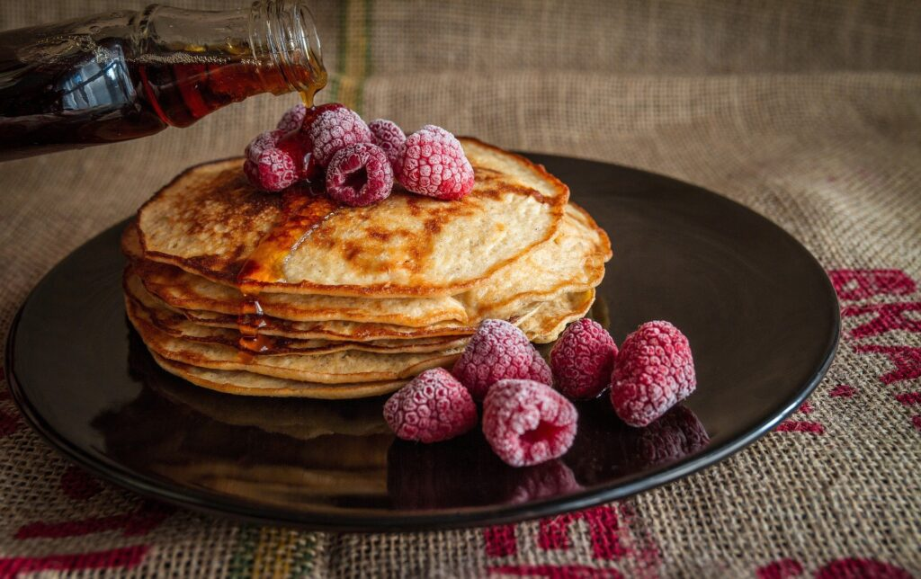 Maple syrup being poured on a stack of pancakes topped with frozen raspberries on a black plate