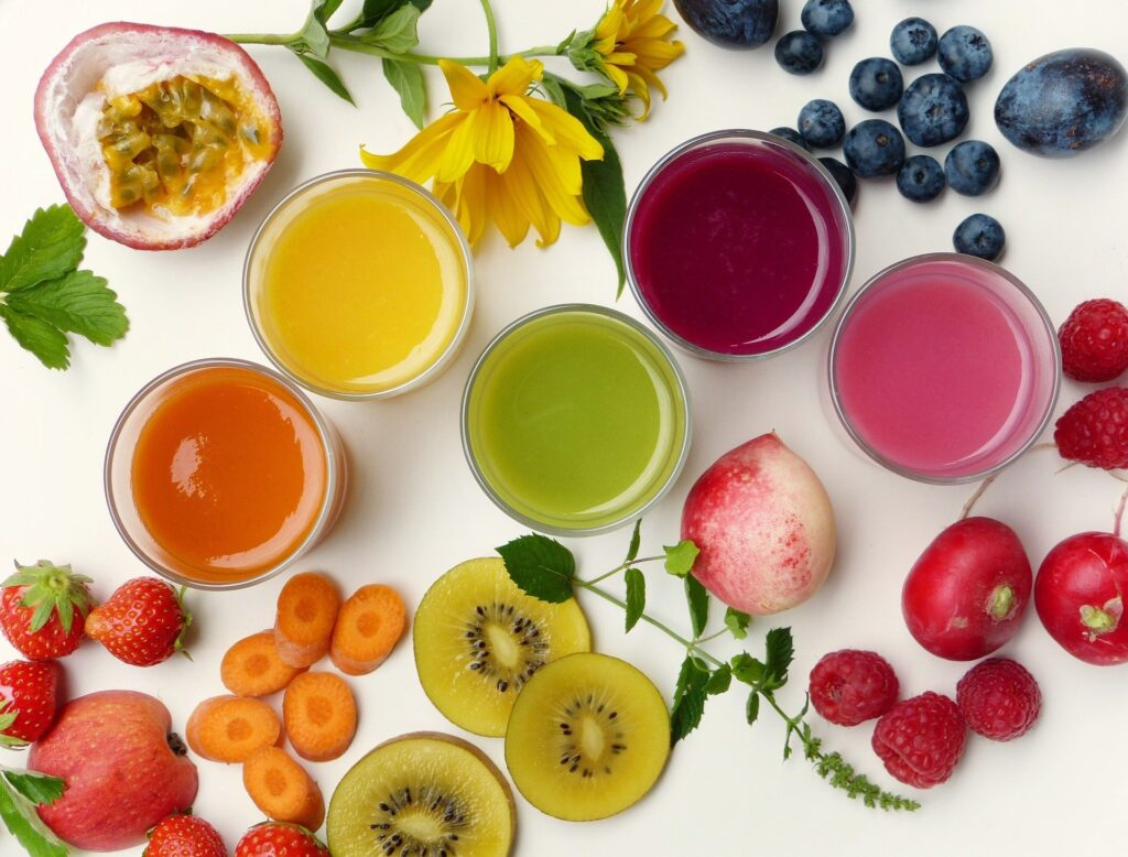Series of different coloured smoothies in glasses surrounded by colourful fruit - breakfast alternatives to cereal