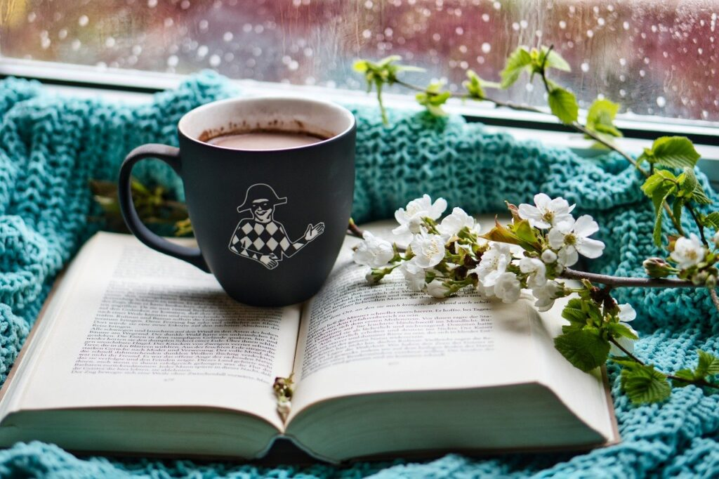Mug of hot chocolate on top of a book surrounded by teal knitwear and white flowers on branches