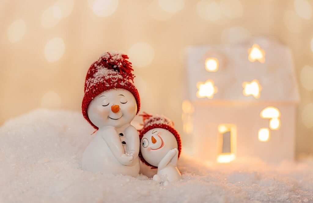 Title image for Fall & Winter Energy Saving Tips - two model snowmen in red woollen hats standing on fake snow in front of a lit white model house