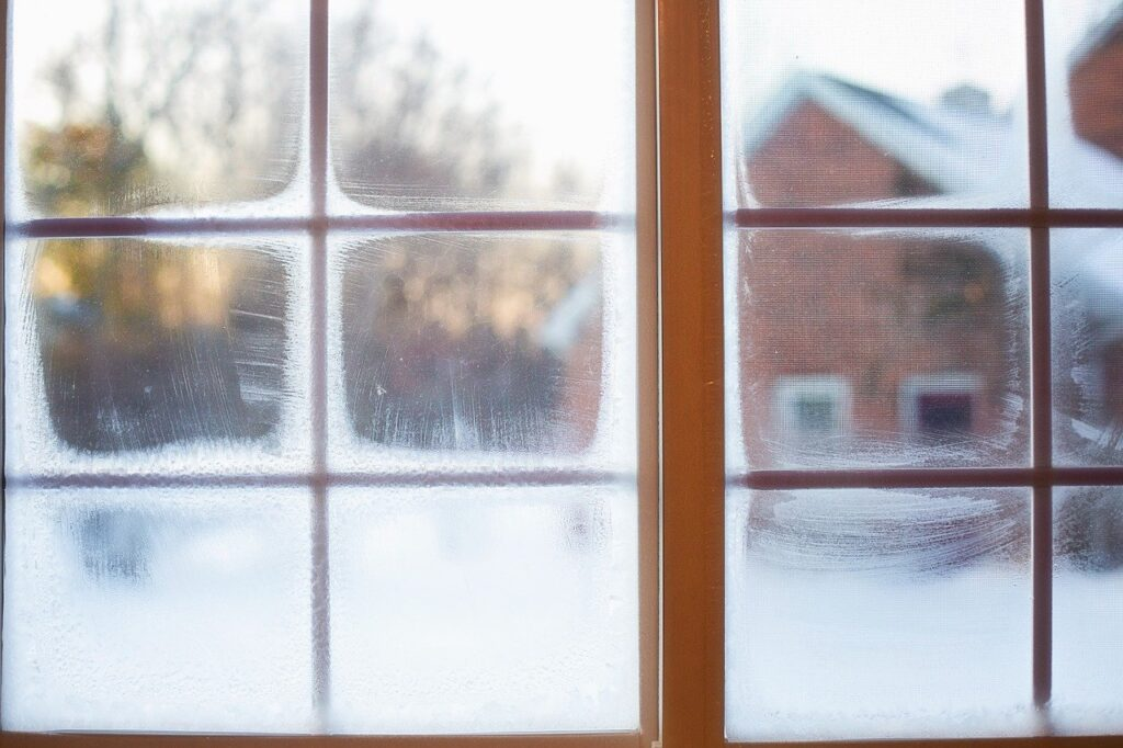 Frosted windows with brown window frames and a snowy outside