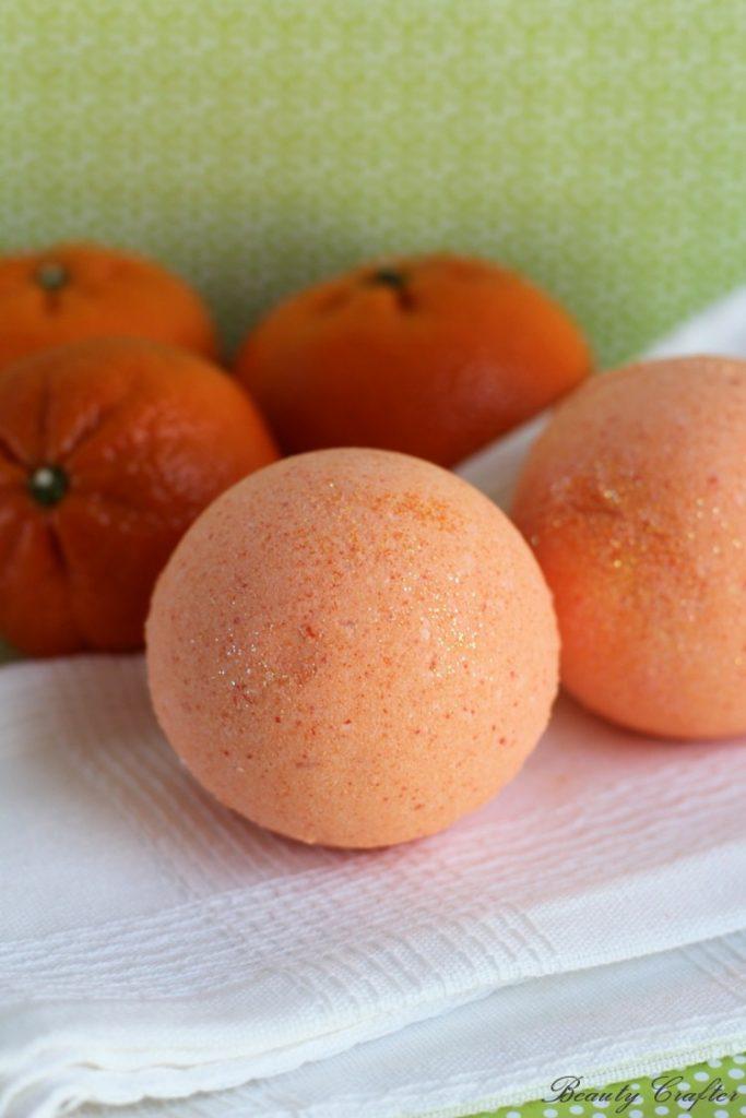 orange bath bombs on a white cloth next to oranges