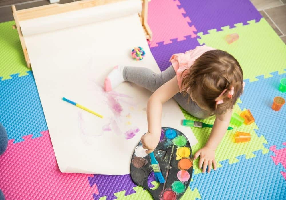 Toddler painting and doing crafts.